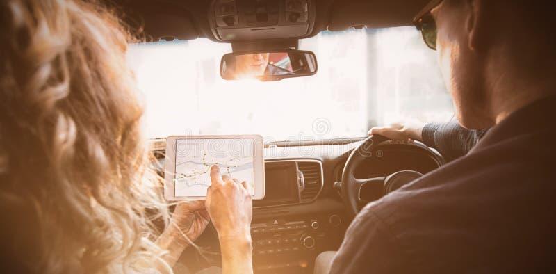 Para patrzeje pastylkę na samochodzie zdjęcia stock