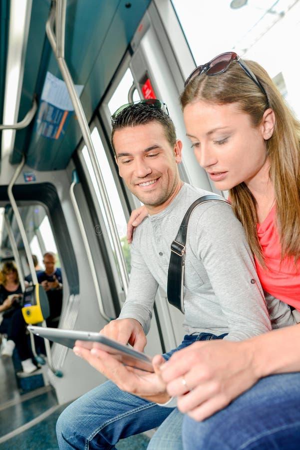 Para patrzeje pastylk? na transporcie publicznym zdjęcie royalty free