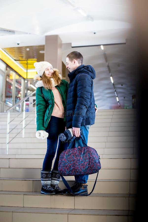 Para podróżnicy w ciepłym odziewa w krokach przy pokojem stacja fotografia royalty free