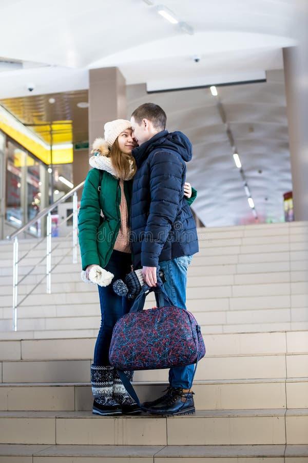 Para podróżnicy w ciepłym odziewa w krokach przy pokojem stacja zdjęcie stock