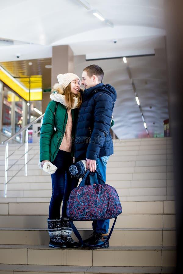 Para podróżnicy w ciepłym odziewa w krokach przy pokojem stacja zdjęcia royalty free