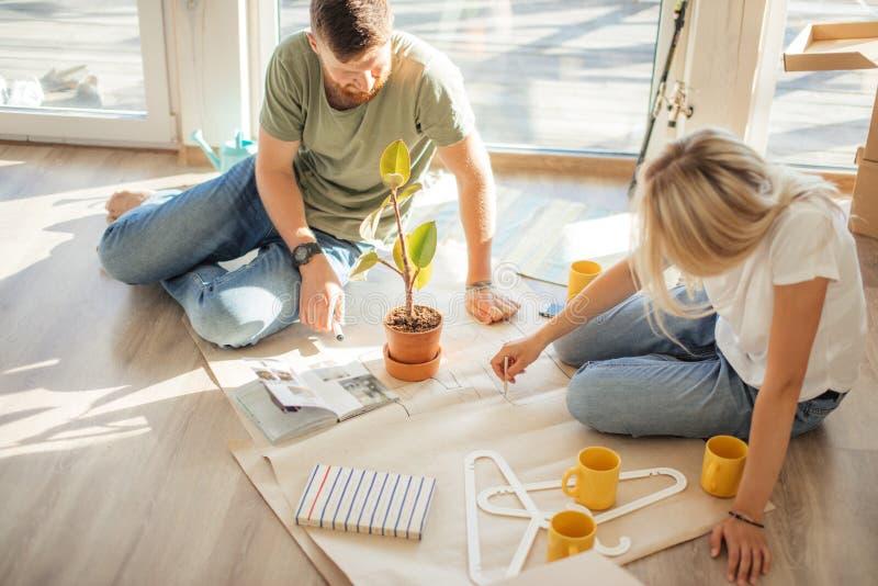 Para przyglądający projekty one nowy dom Planistyczny wewnętrzny projekt obraz stock