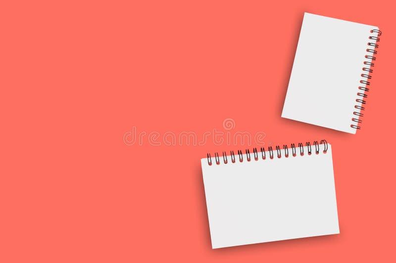 Para pustego papieru notepads z spirala drutem dla notatki lub rysunkiem na tle żywy koralowy kolor zanieczyszczenie na rzecznym  zdjęcie stock