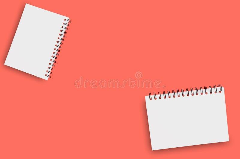 Para pustego papieru notepads z spirala drutem dla notatki lub rysunkiem na tle żywy koralowy kolor zanieczyszczenie na rzecznym  obrazy stock