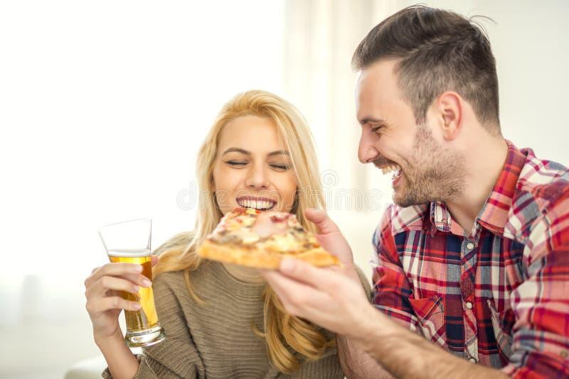 Para relaksuje w domu i je pizzę obrazy royalty free