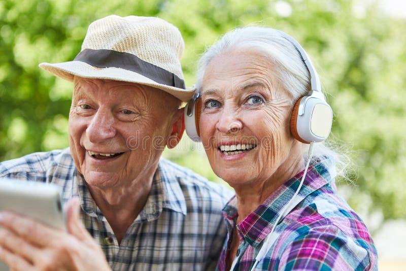 Para seniory z hełmofonami i pastylką zdjęcia royalty free