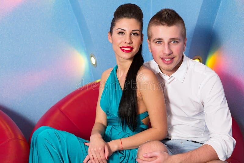 Para siedzi na czerwonym krześle w studiu zdjęcia royalty free