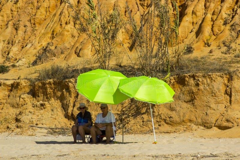 Para siedzi w cieniu brolly na plaży w Portugalia zdjęcia stock