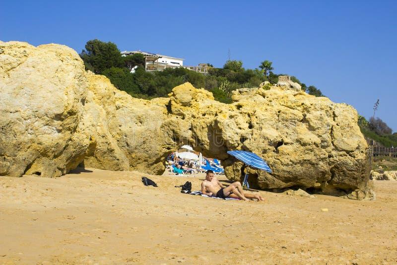 Para siedzi w słońcu obok małego brolly na plaży w Portugalia obrazy stock