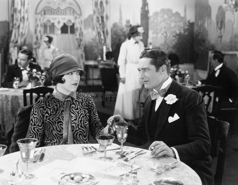 Para siedzi wpólnie w mienia restauracyjnych rękach (Wszystkie persons przedstawiający no są długiego utrzymania i żadny nierucho fotografia stock