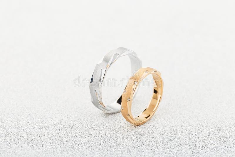 Para srebny mężczyzny pierścionek i menchii złociste kobiety ringowi z diamentami na białym błyskotliwości tle zdjęcia royalty free