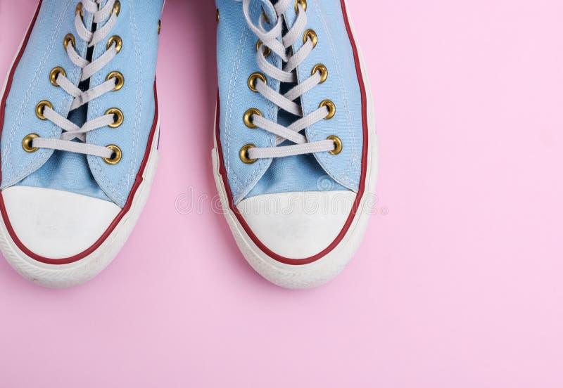 Para starzy będący ubranym błękitni sneakers z biel koronkami na różowym tle obrazy royalty free