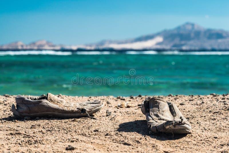 Para starzy podławi buty na piaskowatej plaży Starzy podławi buty na piasku zdjęcie royalty free