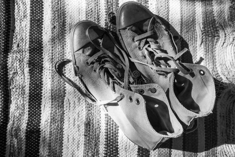 Para starzy sneakers stoi na starym dywanie obrazy stock