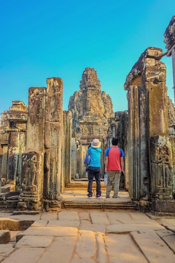 Para stojak przed bayon świątynnym siem przeprowadza żniwa Cambodia obraz royalty free