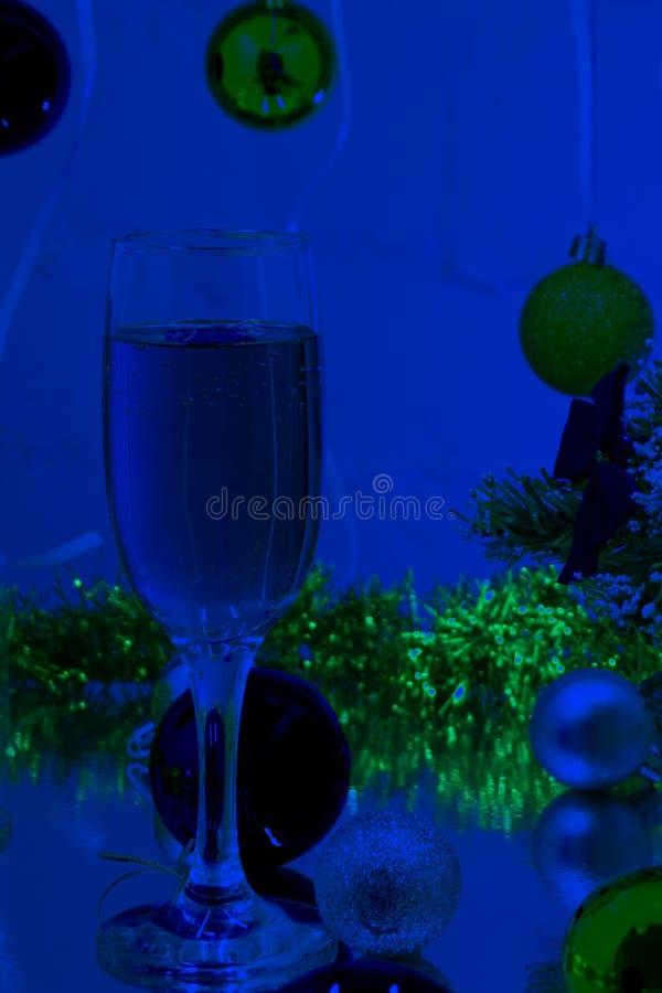 Para szampańscy flety z złocistymi bąblami robi otuchom na błękitnym odcienia światła bokeh tle obraz royalty free