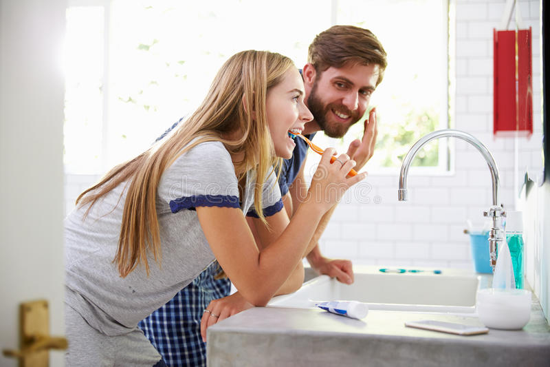 Para Szczotkuje zęby I Stawia Na Moisturizer W piżamach obraz stock