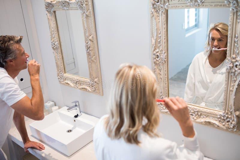 Para szczotkuje zęby przed lustrem zdjęcie royalty free