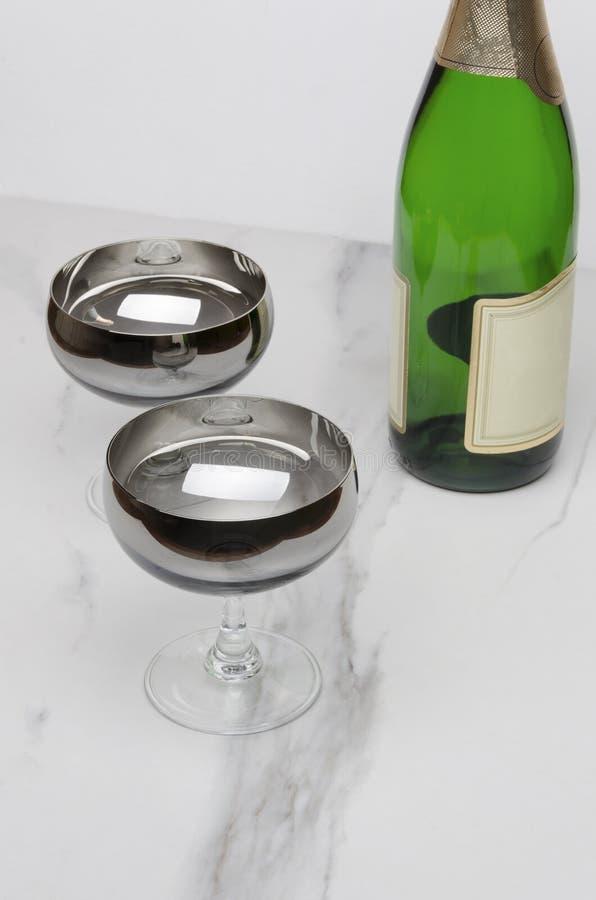 Para szkła, zielona butelka szampan na marmuru stole obraz royalty free
