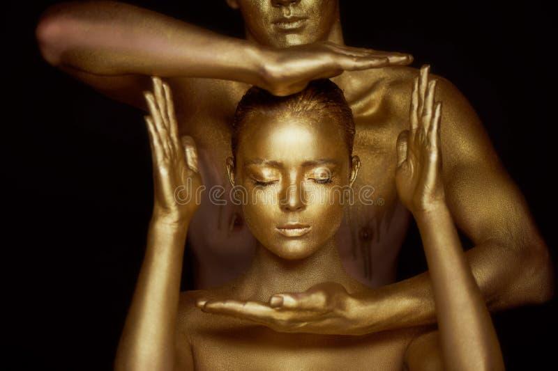 Para tajemniczy młodzi człowiecy, malująca w złocistej farbie Dziewczyny ` s twarz obramia ramą od ręk potomstwa zdjęcia royalty free