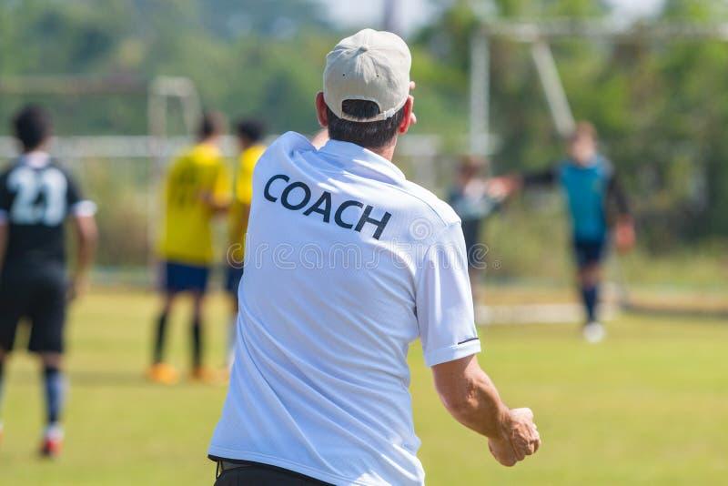 Para trás da camisa vestindo do TREINADOR do treinador de esporte em um campo de esporte exterior fotografia de stock royalty free