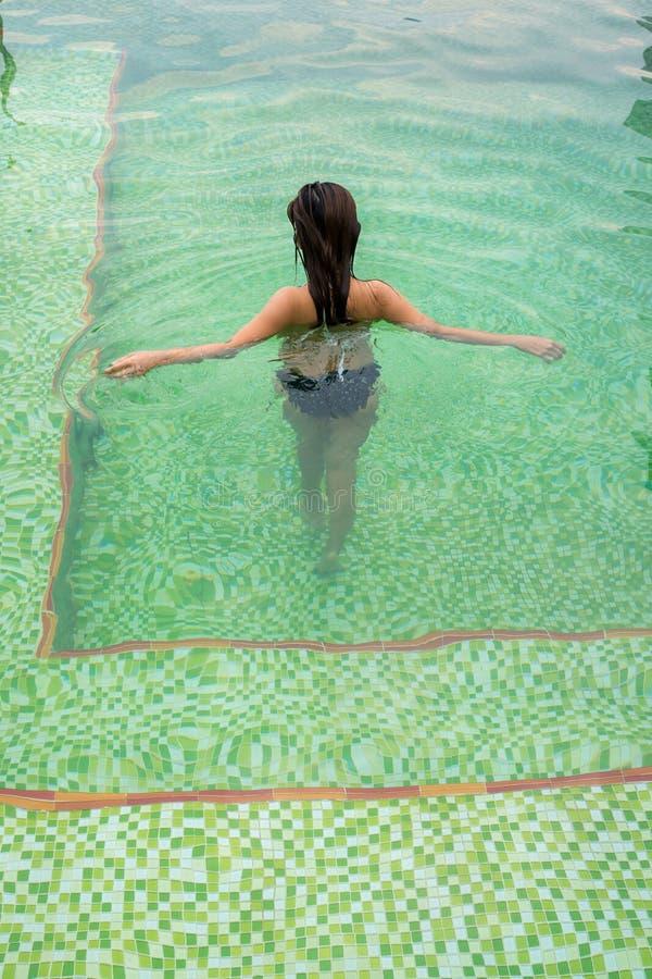 Para trás da menina asiática que anda e que relaxa na piscina fotos de stock royalty free