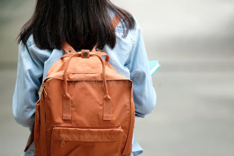Para trás da menina do estudante que guarda os livros e levarem o saco de escola quando wa fotos de stock royalty free
