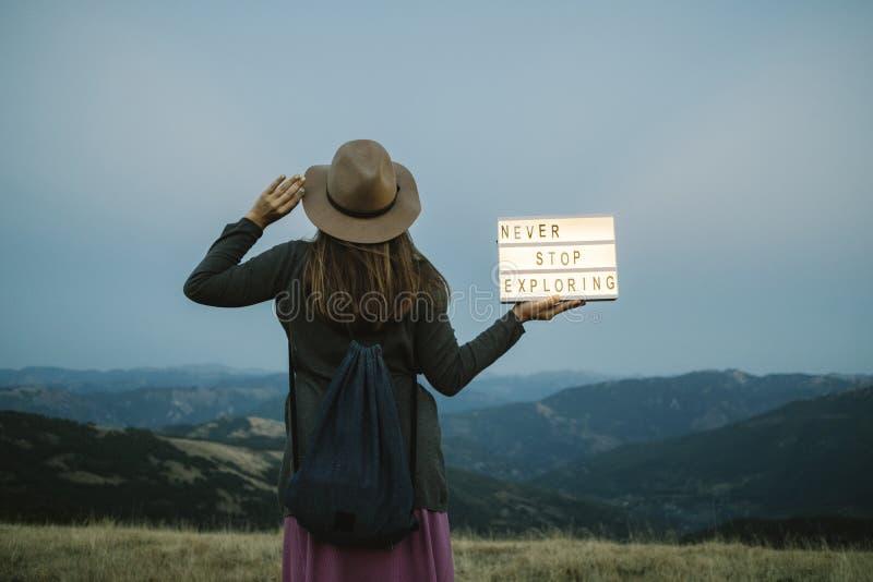 Para trás da mulher com a caixa com texto nunca pare de explorar contra t fotografia de stock royalty free