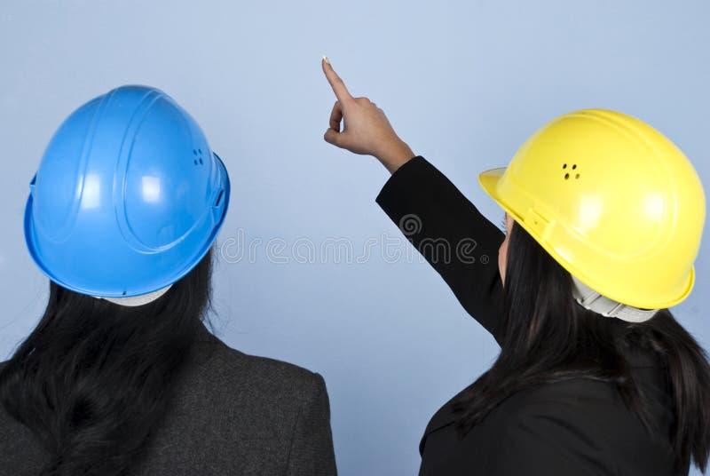 Para trás de duas mulheres dos arquitetos que apontam acima imagem de stock