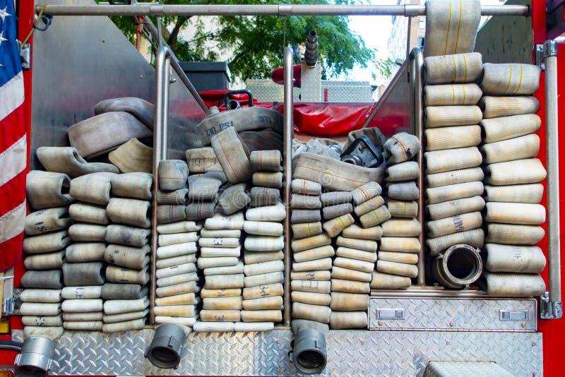 Para trás de um carro de bombeiros com muitos tubos da mangueira da água com americano foto de stock