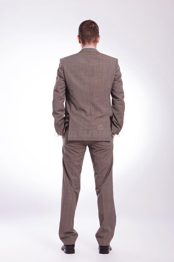 Para trás de um homem de negócio novo com ambas as mãos em uns bolsos imagens de stock royalty free