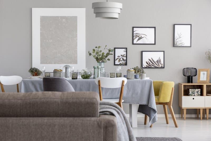 Para trás de um sofá e de uma mesa de jantar com utensílios de mesa, e de uns gráficos em uma parede em um interior diário da sal fotografia de stock
