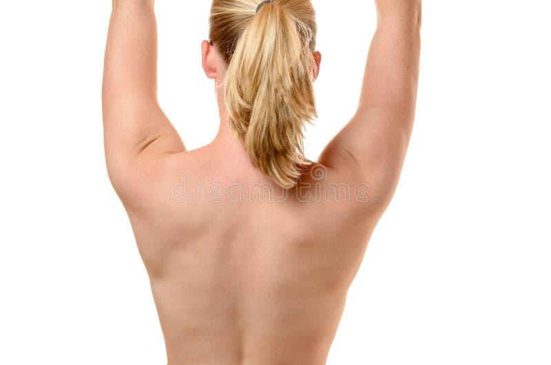 Para trás de uma jovem mulher do ajuste com braços aumentados fotografia de stock