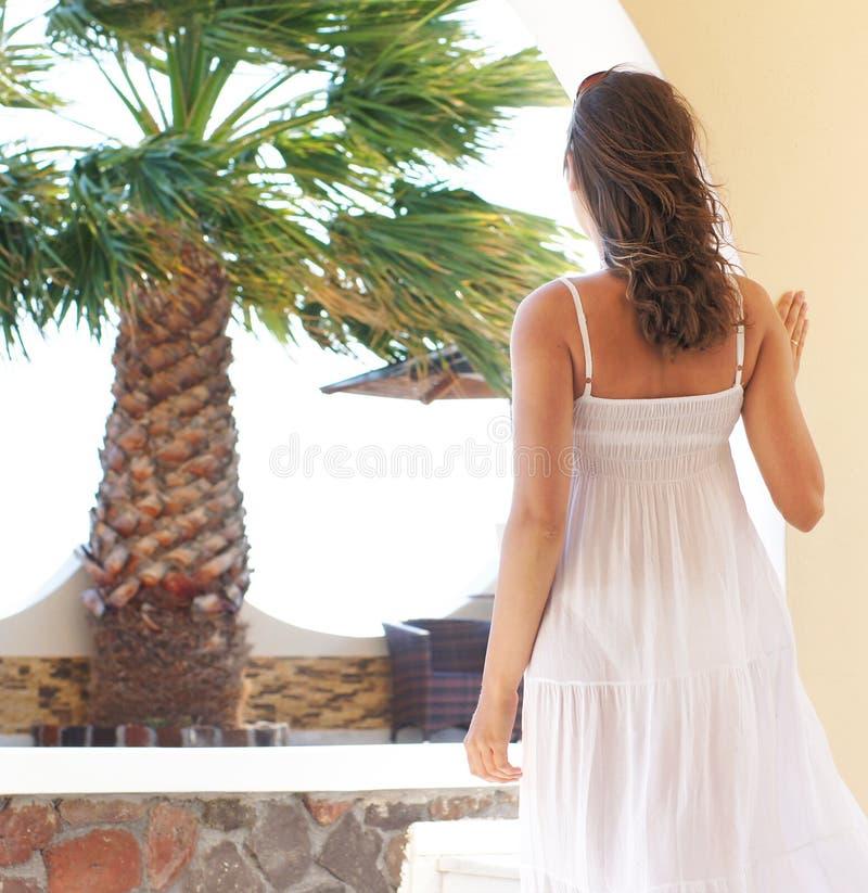 Para trás de uma jovem mulher em um vestido branco em umas férias imagens de stock
