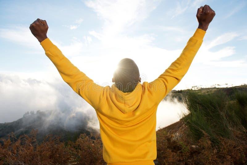 Para trás do homem negro no hoodie com as mãos levantadas no ar e no sol no fundo foto de stock