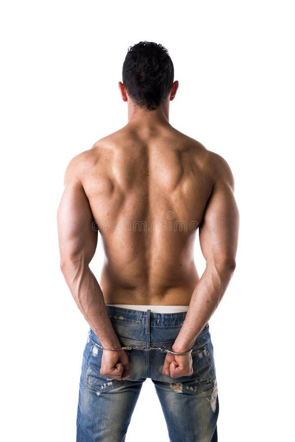 Para trás do homem novo descamisado muscular com algemas fotografia de stock