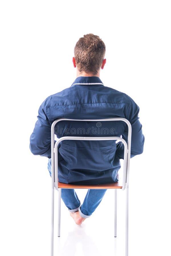 Para trás do homem novo que senta-se na cadeira, isolado fotografia de stock royalty free