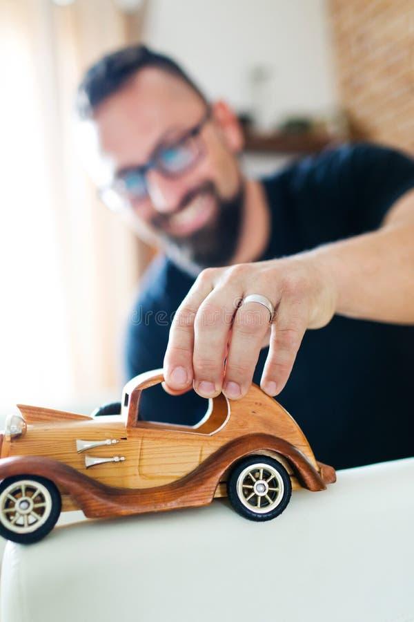 Para trás na infância, homem que joga com o carro de madeira do brinquedo foto de stock royalty free