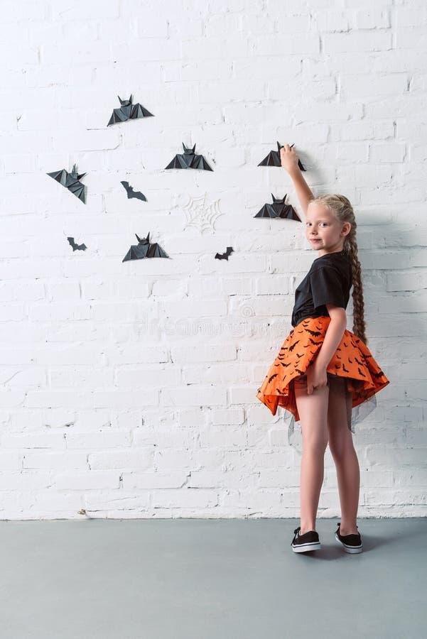 para trás opinião a criança na saia que pendura bastões de papel pretos na parede de tijolo branca o Dia das Bruxas imagem de stock royalty free