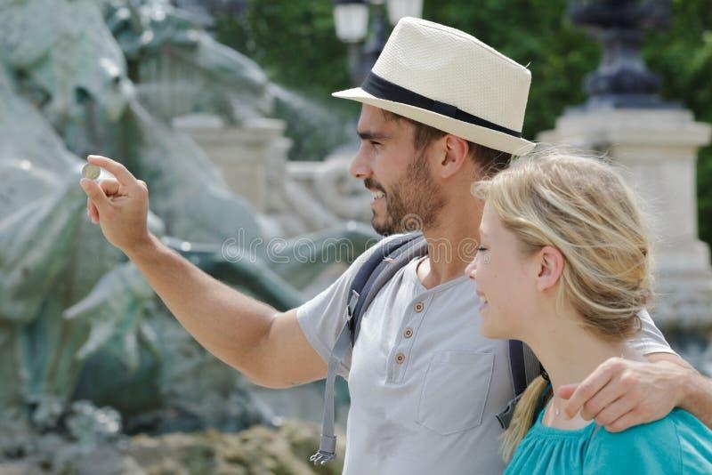 Para turyści rzuca monety w trevi fontanny wodzie obraz stock