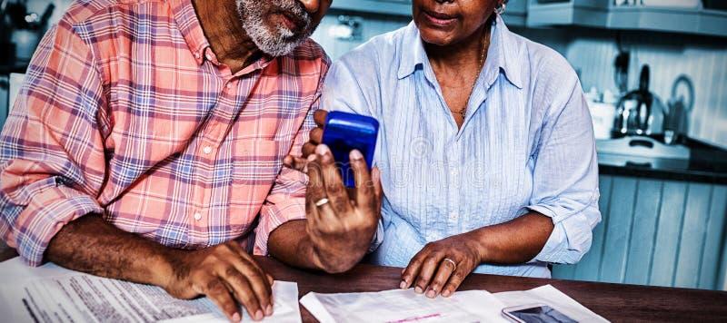 Para używa kalkulatora podczas gdy dyskutujący nad dokumentem fotografia royalty free