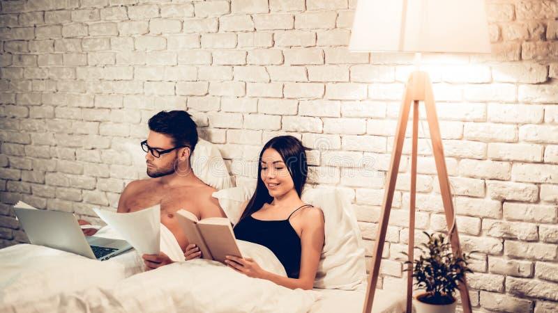 Para Używa laptop Czytelniczą książkę Przed Spać obraz stock