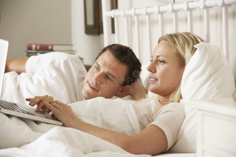 Para Używa laptop W łóżku W Domu obrazy stock
