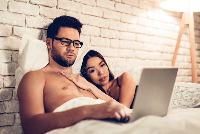 Para Używa laptopu lying on the beach na Łóżkowym dopatrywanie filmu zdjęcie stock