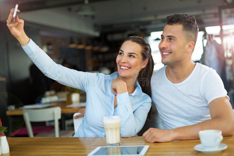 Para używa telefon komórkowego przy kawiarnią fotografia stock