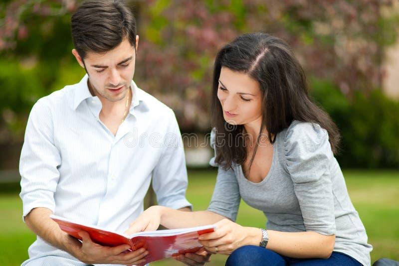 Para ucznie czyta książkę przy parkiem zdjęcie stock