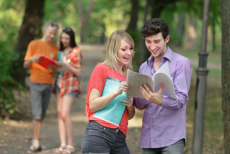 Para ucznie dyskutuje egzamin z schowkiem kwestionuje pozycj? w parku zdjęcia royalty free