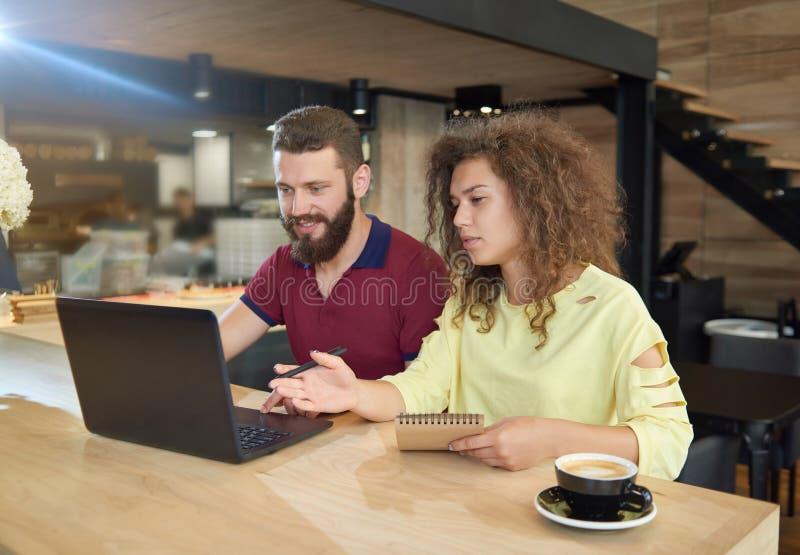 Para ucznie studiuje w cukiernianym używa laptopie fotografia stock
