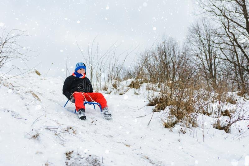 Para un trineo abajo del muchacho en pantalones rojos es muy feliz fotografía de archivo