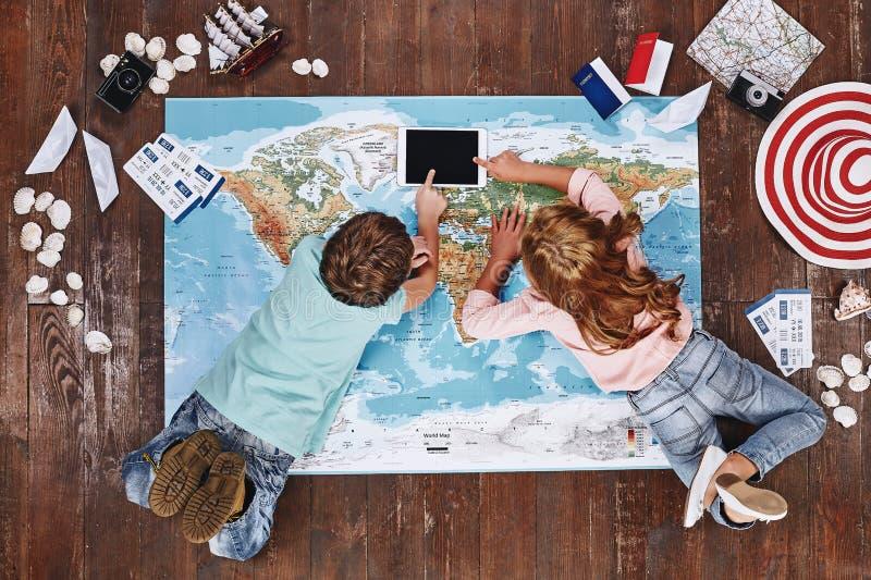 Para viajar é descobrir Crianças que encontram-se no mapa do mundo perto dos artigos do curso e do iPad do toque fotografia de stock royalty free
